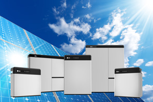group of solar batteries against backdrop of solar panels and blue sky