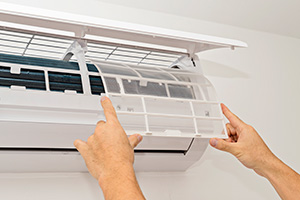 man fitting clean filter into split system