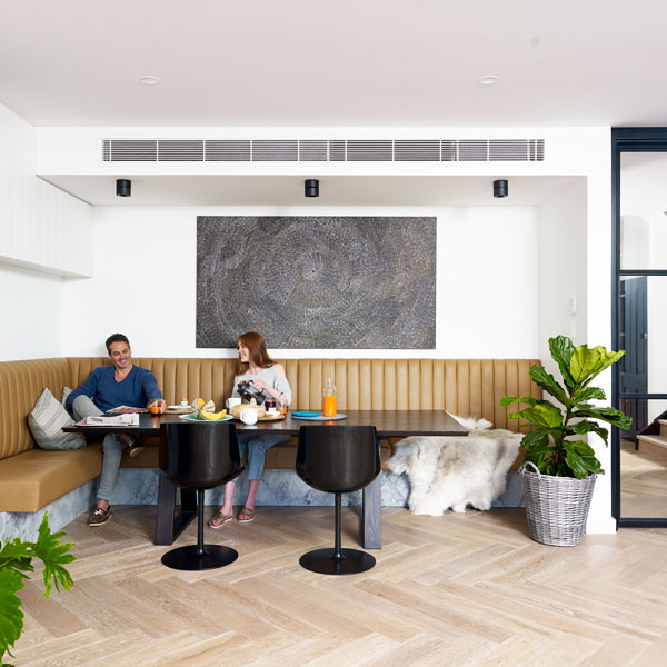 Couple having breakfast under air conditioner ducts in the ceiling