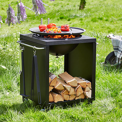 Morso grill with red peppers cooking on top in lush green lawn setting