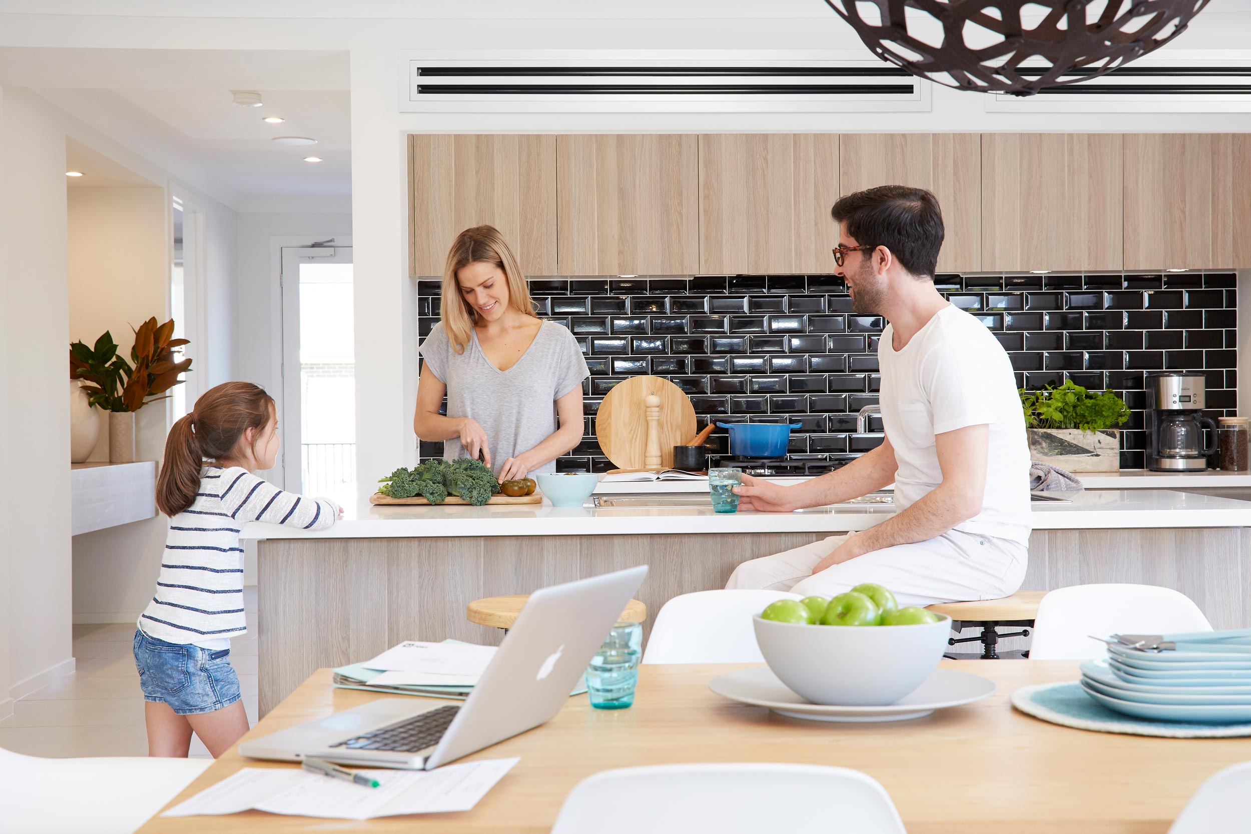 Family of 3 enjoying time in modern kitchen with air conditioning ducts in ceiling
