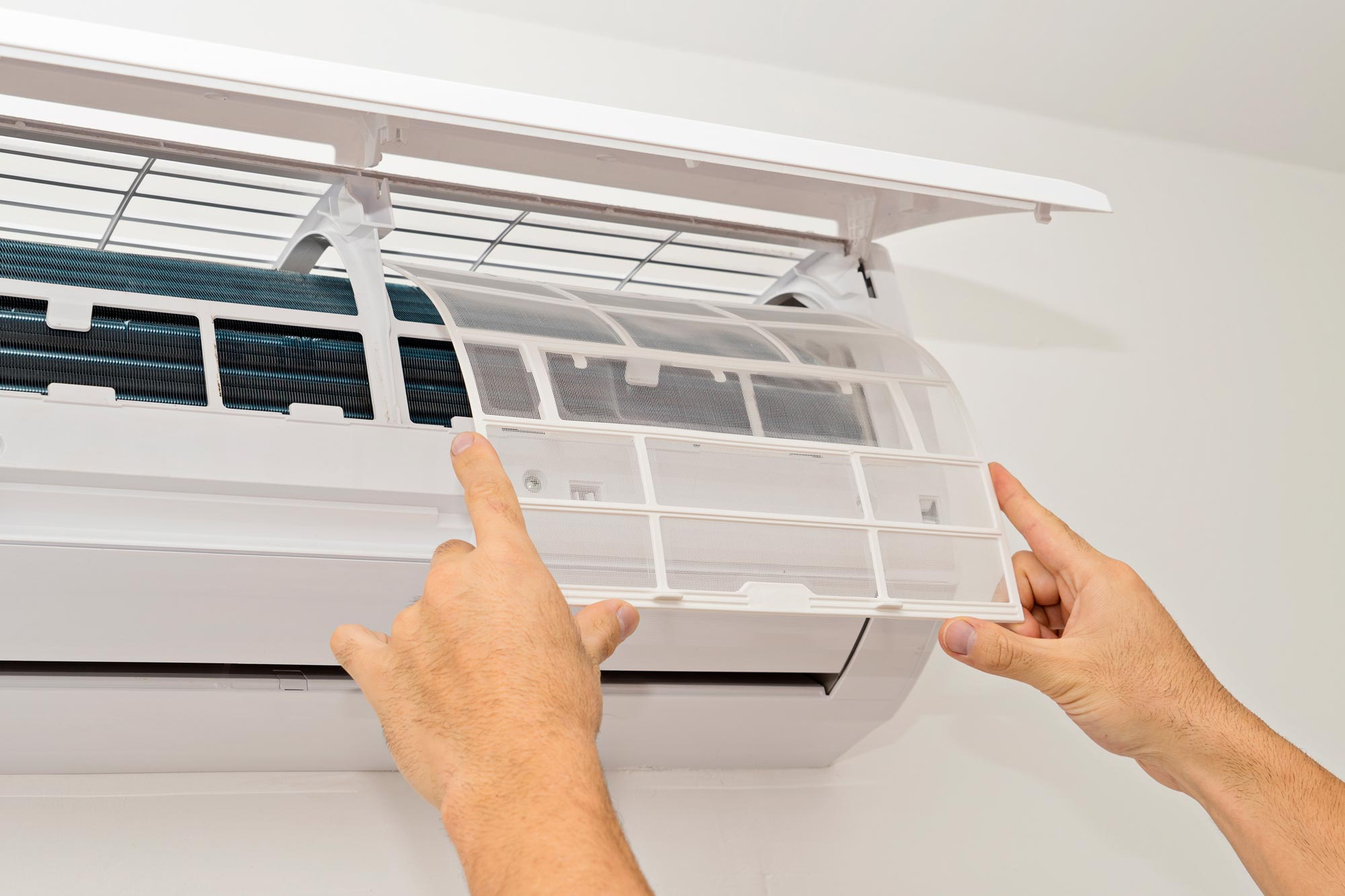Man fitting clean filter back onto wall mounted split system air conditioner