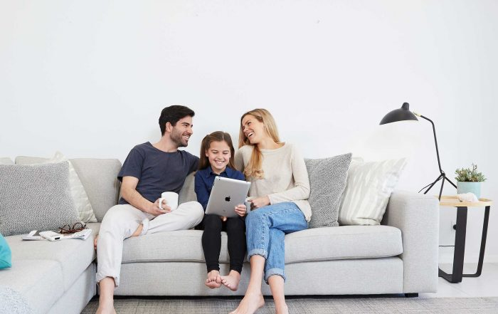Family relaxing in loungeroom with Daikin split system air conditioner on