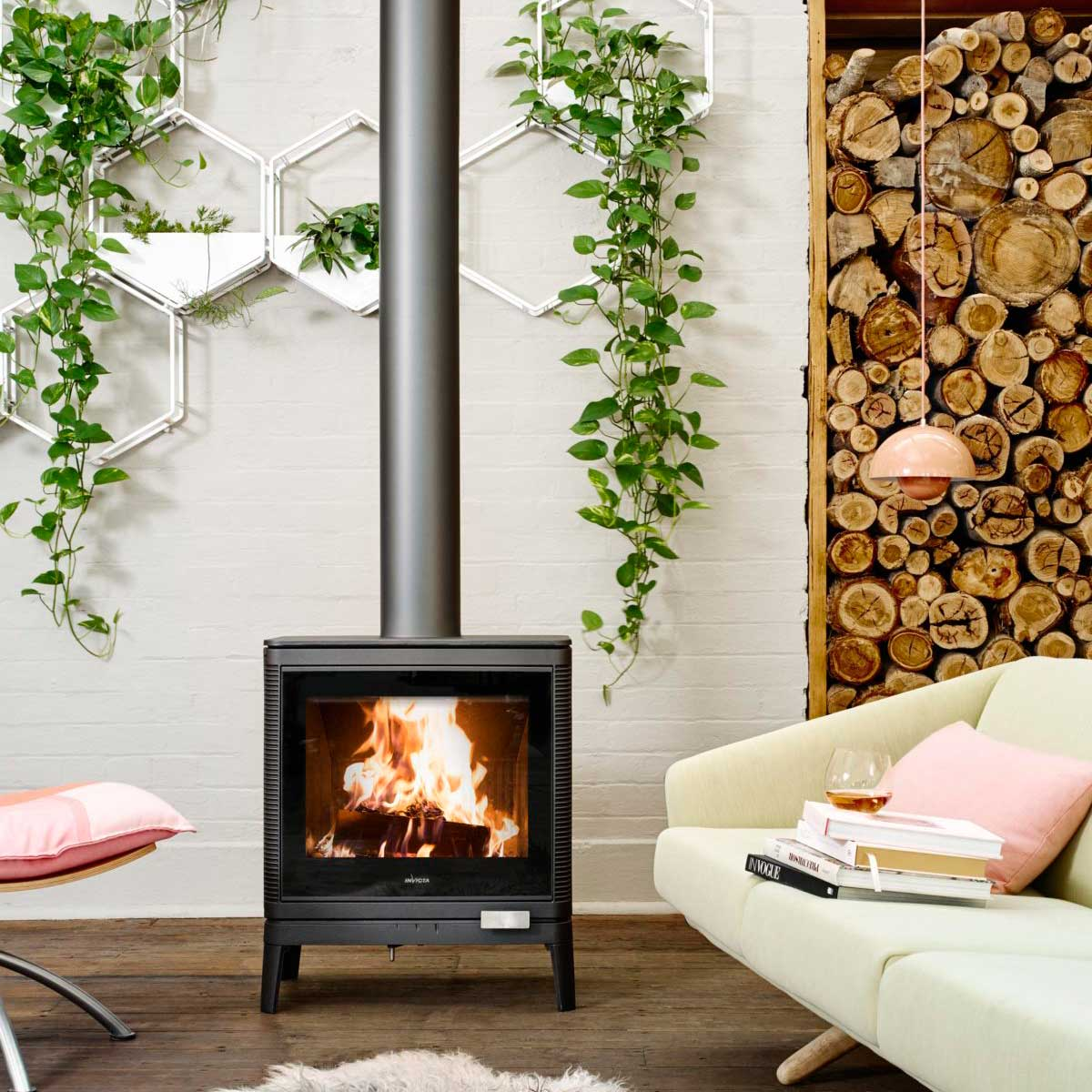 Invicta Kazan wood heater in beautiful interior setting with contemporary white lounge, pink cushions and lush indoor plants