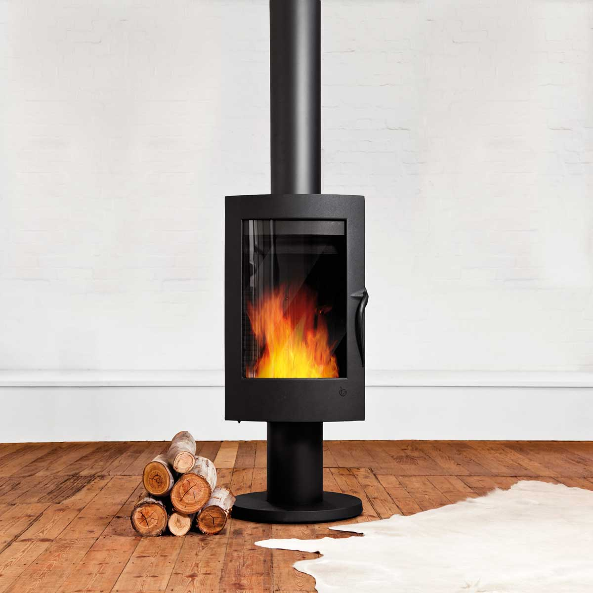 Invicta Pharos wood heater in minimalist room with white walls and timber floor