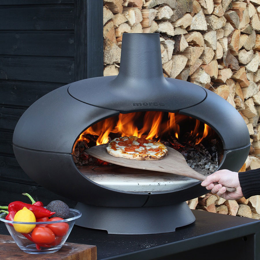 Morso Forno outdoor oven with wood fired pizza inside on a bamboo pizza paddle