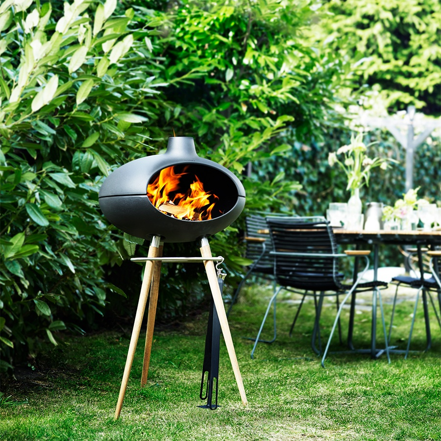 Morso Forno grill and outdoor oven on timber tripod legs in lush green outdoor setting