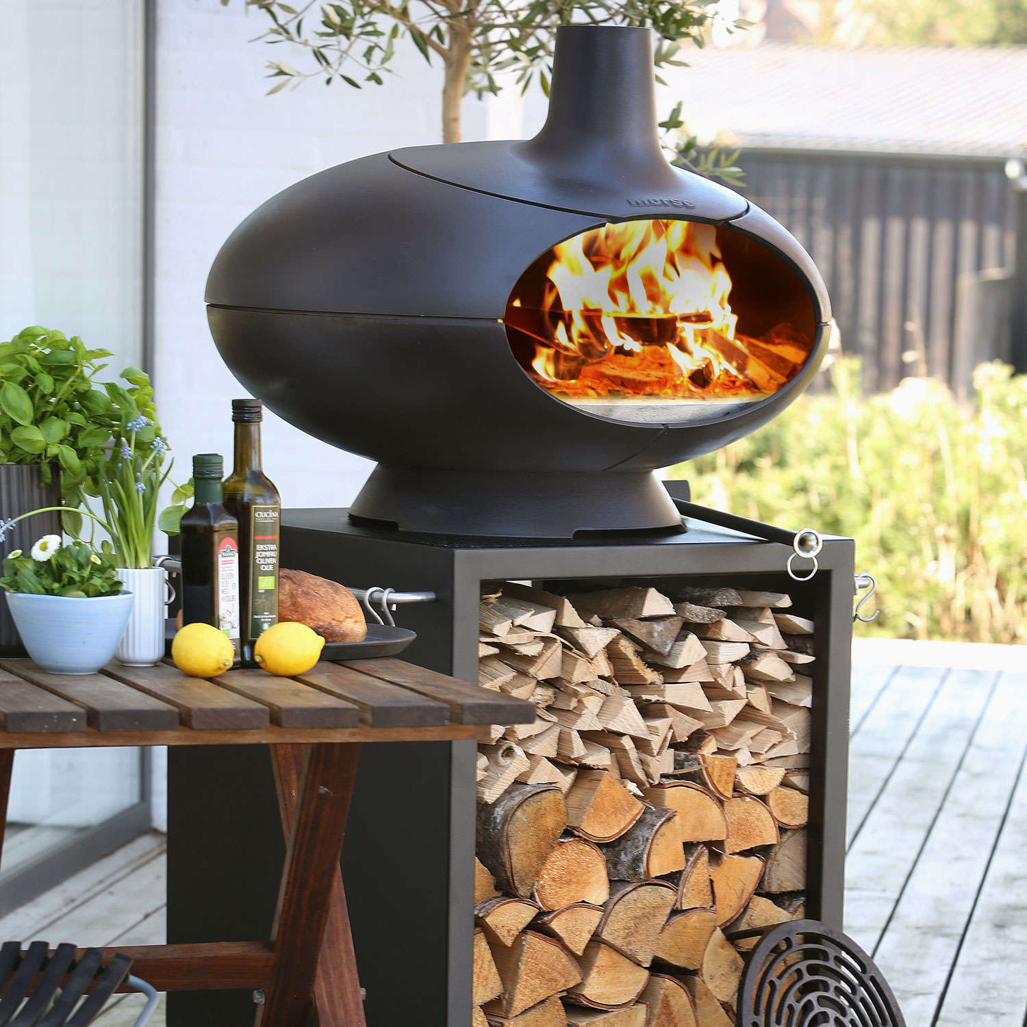 Morso Forno Terra outdoor oven set next to cooking ingredients such as olive oil, lemons and fresh herbs